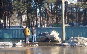 В Киеве так затопило дорогу, что машина провалилась под асфальт: появились фото