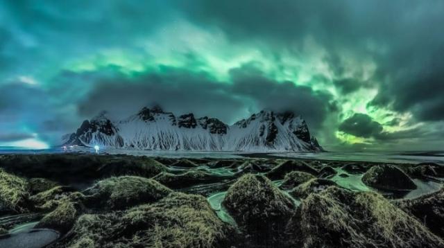 Аврора Бореалис прорывается сквозь облака и нависает над горами в Стоккнесе.