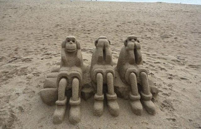 Три мудрые обезьяны на пляже в Барселоне.