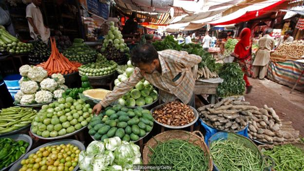 A vendor arranges vegetables at a local market in Karachi, Pakistan