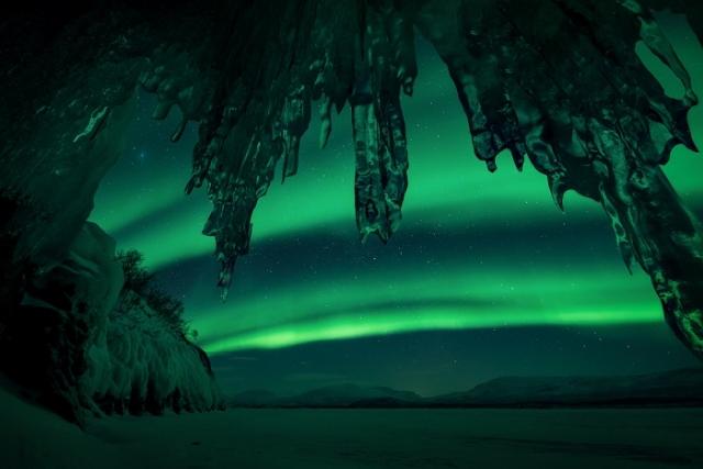 Северное сияние отражает оттенки зеленого и желтого на снегу, как видно из крошечной пещеры на озере Торнетраск, в Лапландии.
