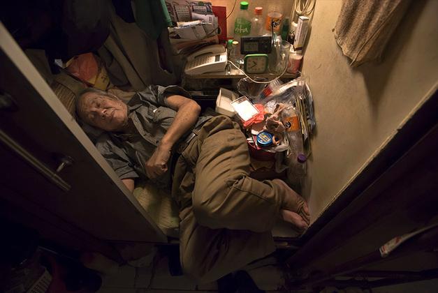 80-летний Чхён Чхифон спит в своей комнате-гробе — так зачастую называют тесные комнатушки в гонконгских коммуналках. Их размер настолько мал, что там невозможно вытянуть ноги.