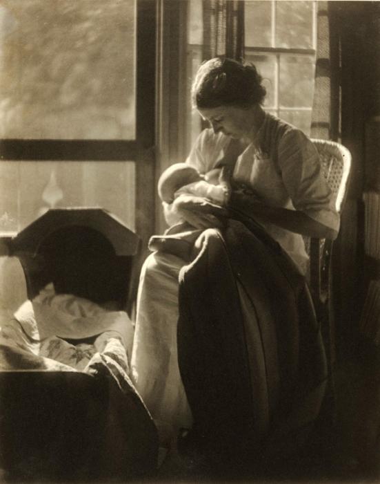 Мама возле колыбели увлеченно кормит младенца.